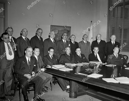 """Stock Photo of Members of the Wage Adjustment Board, a """"little war labor board"""" reconstituted by the War Labor Board to handle wage adjustments in the building trades and construction industries as they held their first meeting at the Department of Labor in Washington on . Left to right seated: James D. Marshall, Washington, D.C.; Louis C. Sherman, Washington, D.C. Arthur D. Hill, Jr., Washington, D.C.; D. W. Tracy, Assistant Secretary of Labor and Chairman of the Board; George S. McGahan, Executive Secretary of the Board; Edgar Warren, Washington, D.C.; and Robert Lynch, Washington, D.C.; Standing: John J. McCurry, Washington, D.C.; J.S. Miller, Pittsburgh Penn.; Michael Garrett, Washington, D.C.; Stephen D. Butts, Detroit, Michigan; Paul M. Geary, Washington, D.C.; H. R. Cole, Washington, D.C.; Herbert Rivers, Washington, D.C.; John W. Garvey, Washington, D.C.; Robert Byron, Washington, D.C. and Harry C. Bates, Washington, D.C"""