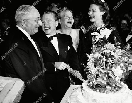 Stock Photo of Film actor Mickey Rooney celebrates his 21st birthday at a party in a Hollywood night club. Here he slices his birthday cake with (left to right) Louis B. Mayer, studio head; Mrs. Nell Pankey, his mother, and Miss Ava Gardner. Mickey's father, Joe Yule, is at the right in the background