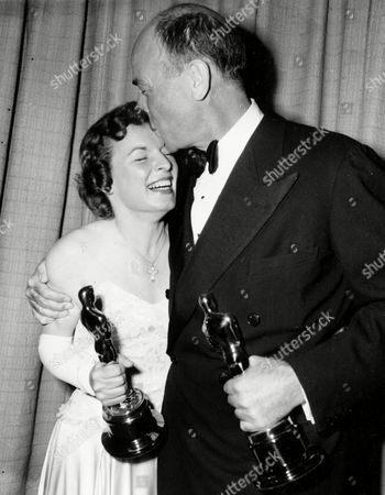 Best supporting actor Dean Jagger plants a kiss on the forehead of best supporting actress Mercedes McCambridge, as they pose with their Oscars at the Academy Awards ceremony in Hollywood, Calif., on