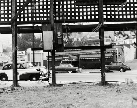 Sheriff's deputies investigating the shooting of gambler Mickey Cohen and three others as they were leaving Sherry's cafe (background), in Hollywood, . Theorized the gunmen stood beneth the sign in foreground. The four shooting victims, Cohen, Harry Cooper, a special agent assigned by the Attorney General's office to protect actress Dee David, were reported to be recovering July 21 from their wounds
