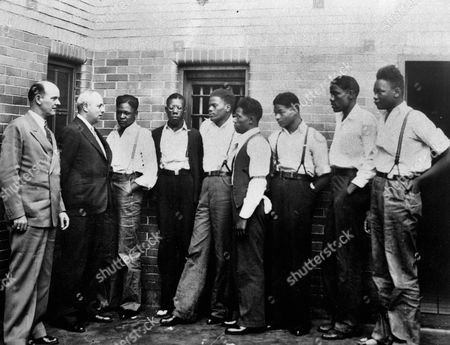 Attorney Samuel Leibowitz from New York, second left, meets with seven of the Scottsboro defendants at the jail in Scottsboro, Ala. just after he asked the governor to pardon the nine youths held in the case. From left are Deputy Sheriff Charles McComb, Leibowitz, and defendants, Roy Wright, Olen Montgomery, Ozie Powell, Willie Robertson, Eugene Williams, Charlie Weems, and Andy Wright. The black youths were charged with an attack on two white women on March 25, 1931