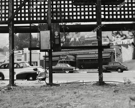 Watchf Associated Press Domestic News California United States APHS38154 SHOOTING SCENE Sheriff's deputies investigating the shooting of Gambler Mickey Cohen and three others as they were leaving Sherry's Cafe (background), in Hollywood, Calif., theorized the gunmen stood beneath the sign in foreground. The four shooting victims, Cohen, Harry Cooper, A special agent assigned by the Attorney General's office to protect Cohen, Edward(Neddie) Herbert, and actress Dee David, were reported to be recovering July 21, from their wounds