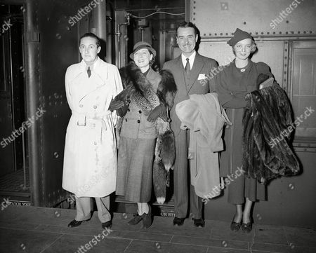 Stock Photo of Irving Thalberg, director, his wife, Norma Shearer, actress, and John and Virginia Gilbert, from left to right are, photographed in New York City, when they arrived from the coast, . Gilbert and his wife, the former Virginia Bruce, actress, expect to sail soon for a trip in Europe. They were married