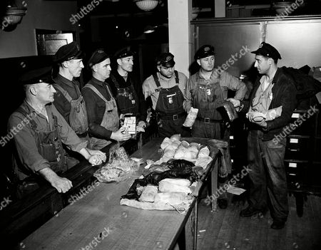 """James Maloney, Tim Driscoll, Eugene Dorney, John Boyce, Max Borovy, Ernest Stahl, Frank Sortino Workers at the U.S. Customs Service in New York City look over a table stacked with packages of heroin, opium and perfume, valued at $300,000, after the contraband had been seized in a search of the Liberty ship Bastia, . The ship is owned by the Sabre Line of France. Customs men charged that Charles """"Lucky"""" Luciano was involved in this and every other recent such shipment. Customs workers, from left: James Maloney, Tim Driscoll, Eugene Dorney, John Boyce, Max Borovy, Ernest Stahl and inspector Frank Sortino"""