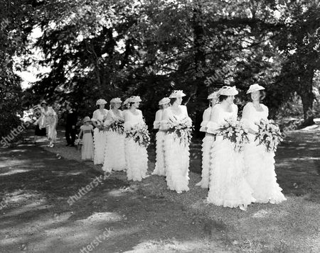 Attendants for Margaret McGrath, daughter of Mr. and Mrs. Francis Sims McGrath of Mount Kisco, New York, begin the wedding march outside St. Matthew?s Church at Bedford, New York, where she married David Rockefeller, youngest son of Mr. and Mrs. John D. Rockefeller, Jr. Attendants were Charlotte Keidel, Baltimore; Lillias Dulles, Alice Otis and Helene Thomson of New York; Mary Duane Humphreys and Deborah Humphreys and Mount Kisco; Mrs. Alex Ander Vietor of New York and Mrs. Craig Wylie of Concord, N.H. The Bride?s sister, Eileen, was maid of honor