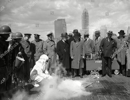 ARB crew on 21st floor terrace of the Empire State building in New York on demonstrates how they will fight incendiary bombs. From left to right are Lt. Col. F. K. Johnson, representing commandant, 1st interceptor Army Air Corps; Maj. Neal J. D'Brien, adjudant General's Dept. U.S. Army; Col. Arthur V. McDermott, Dir. Selective Service for N.Y. City; former Governor Alfred E. Smith; Lt. Gov. Charles Poletti, Vice Chairman. National and State council of Defense and other officials