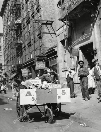 Helen Goodman of the American Women's Voluntary Services with headquarters at the Grand Street Settlement Annex, collects scrap metal, rubber and other salvage for war material in a pushcart, because of the gasoline and rubber shortage on the Lower East Side, New York, . Previously A.W.V.S. members donated private automobiles for such pickups