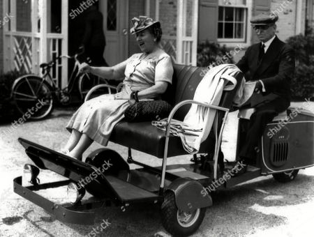 Mrs. Stuart Duncan, Newport, R.I., society leader, laughs as she rides along in her gas-saving buggy driven from the rear by her goggled and kid-gloved chauffeur in Newport, Rhode Island on . The specially designed vehicle is powered by a small scooter motor beneath the chauffeur