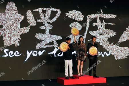 """Hong Kong actor Tony Leung, left, Hong Kong actress Angelababy, center, and Taiwan-Japanese actor Takeshi Kaneshiro holding medals pose for photographers during a press conference for their latest movie """"Ferryman"""" in Beijing, . The movie will open in China on Dec. 23"""