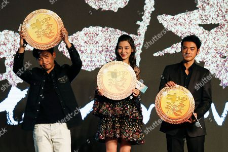 """Hong Kong actor Tony Leung, left, Hong Kong actress Angelababy, center, and Taiwan-Japanese actor Takeshi Kaneshiro pose with medals on stage during a press conference for their latest movie """"Ferryman"""" in Beijing, . The movie will open in China on Dec. 23"""