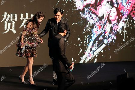 """Hong Kong actor Tony Leung, bottom, and Taiwan-Japanese actor Takeshi Kaneshiro, top right, help Hong Kong actress Angelababy walk down from a stage during a press conference for their latest movie """"Ferryman"""" in Beijing, . The movie will open in China on Dec. 23"""