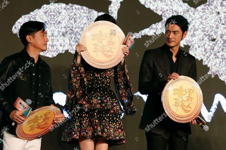 """Hong Kong actor Tony Leung, left, and Taiwanese-Japanese actor Takeshi Kaneshiro, right, look at Hong Kong actress Angelababy uses a medal to cover her face after they receive them from Hong Kong director Wong Kar-wai during a press conference for their latest movie """"Ferryman"""" in Beijing, . The movie will open in China on Dec. 23"""