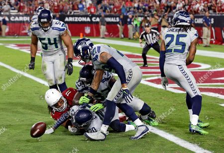 Stock Photo of Seattle Seahawks cornerback Richard Sherman (25), free safety Earl Thomas (29), middle linebacker Bobby Wagner (54) strong safety Kelcie McCray (33) and cornerback Jeremy Lane (20) knock the ball away from Arizona Cardinals wide receiver Larry Fitzgerald (11) as overtime expires during an NFL football game, in Glendale, Ariz. The game ended in overtime in a 6-6 tie