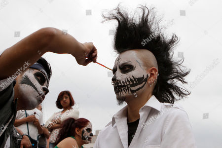 """Cristian Jimenez paints the face of his brother Jose Luis Castillo to resemble a """"calavera,"""" or skull face, in preparation for the Gran Procession of the Catrinas, to mark the upcoming Day of the Dead holiday, in Mexico City, . The gran procession is one of many that will take place in Mexico City as part of the celebrations, culminating with visits to the graves of departed loved ones on Nov. 1 and 2. The figure of a skeleton wearing broad-brimmed hat was first done as a satirical engraving by artist Jose Guadalupe Posada sometime between 1910 and his death in 1913, to poke fun at women who pretended to be European by dressing elegantly and as a critique of social stratification"""