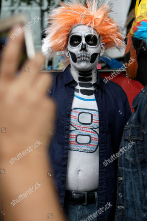 Carlos Ramirez, dressed as a calavera, poses for a photo as he waits for the start of the Gran Procession of the Catrinas, to mark the upcoming Day of the Dead holiday, in Mexico City, . The gran procession is one of many that will take place in Mexico City as part of the celebrations, culminating with visits to the graves of departed loved ones on Nov. 1 and 2. The figure of a skeleton wearing broad-brimmed hat was first done as a satirical engraving by artist Jose Guadalupe Posada sometime between 1910 and his death in 1913, to poke fun at women who pretended to be European by dressing elegantly and as a critique of social stratification