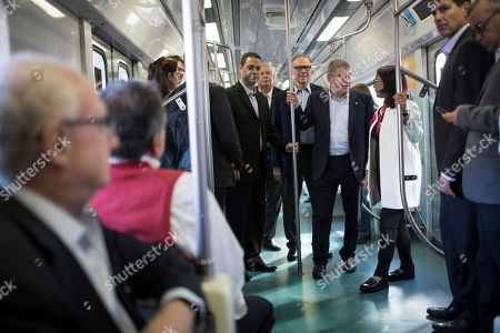 IOC President Thomas Bach, fourth from right, talks to the head of the International Olympic Committee's evaluation commission Nawal El Moutawakel, in a train on their way to the Deodoro Olympic Complex in Rio de Janeiro, Brazil, . Rio will host the Olympic games starting on Aug. 5, amid the worst recession to hit Brazil in decades, an outbreak of the Zika virus and the ongoing political crisis that saw President Dilma Rousseff impeached and suspended from office