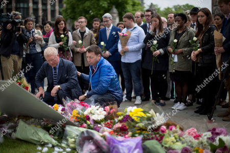 Staff from Britain's opposition Labour Party including at the front MP John Cryer, left, the Chair of the Parliamentary Labour Party and Iain McNicol, right, the party's General Secretary pay their respects after placing floral tributes for their colleague Jo Cox, the 41-year-old British Member of Parliament shot to death yesterday in northern England, on Parliament Square outside the House of Parliament in London, . The married mother of two young children was shot to death Thursday afternoon in her constituency near Leeds, in northern England. Thomas Mair, 52, was arrested Thursday on suspicion of killing Cox, outside a library