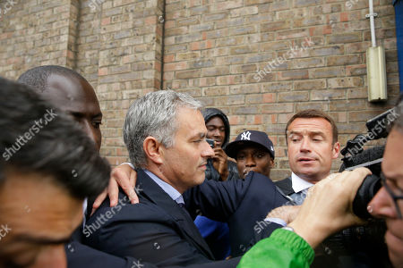 Former manager of Chelsea soccer team and current manager of Manchester United Jose Mourinho, centre, is escorted through the media to get to a car as he leaves after attending an employment tribunal for former Chelsea team doctor Eva Carneiro at the Croydon Employment Tribunal in Croydon, south London, . Chelsea has reached a settlement with its former club doctor at the start of an employment tribunal, details were not disclosed Tuesday