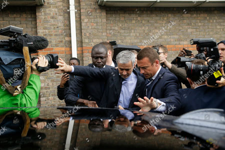 """Former manager of Chelsea and current manager of Manchester United Jose Mourinho, centre, tries to get in the back of a car as he leaves after attending an employment tribunal for former Chelsea team doctor Eva Carneiro at the Croydon Employment Tribunal in Croydon, south London, . Chelsea has reached a settlement with its former club doctor at the start of an employment tribunal, details were not disclosed Tuesday. Carneiro was dropped from first-team duties after Mourinho accused the medical staff of being """"naive"""" for treating Eden Hazard on the field with Chelsea already down to 10 men in last season's Premier League opener in August"""