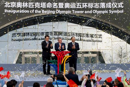 From left to right, Beijing Mayor Wang Anshun, International Olympic Committee (IOC) President Thomas Bach, and Liu Peng, Minister of the General Administration of Sport of China applause on stage after the inauguration of the Beijing Olympic Tower and Olympic Symbol in Beijing, . Beijing will host the Winter Olympics in 2022