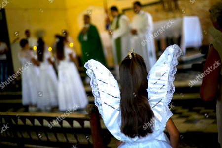 Stock Picture of Veronica Hernandez, dressed as an angel, attends a Mass celebrated by the new archbishop of Havana Juan de la Garcia Caridad Rodriguez in Jaruco, Cuba