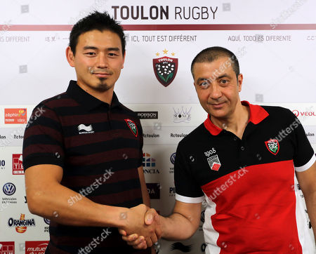 Japan's rugby player Ayumu Goromaru, left, shakes hands with RCT team owner Mourad Boudjellal during a press conference at the Mayol stadium of Toulon, southern France, . The 30-year-old signed to Toulon on a one-year contract with a 12 month extension as an option