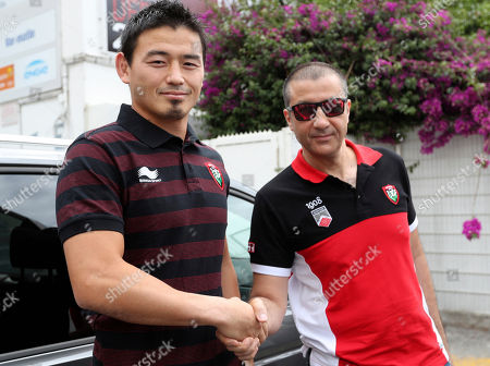 Japan's rugby player Ayumu Goromaru, left, shakes hands with RCT team owner Mourad Boudjellal before a press conference at the Mayol stadium of Toulon, southern France, . The 30-year-old signed to Toulon on a one-year contract with a 12 month extension as an option