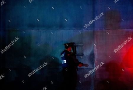 """A police officer communicates through a barred window in the entrance gate to the airport hangar of Mexico's Attorney General office, in Mexico City, after the arrival of drug lord Hector """"El Guero"""" Palma, . Palma, one of the founders of the Sinaloa Cartel, returned to his native country Wednesday after serving almost a decade in a U.S. prison. U.S. authorities handed over Palma in Matamoros, across the border from Brownsville, Texas, before flying him to Mexico City for transfer to Altiplano maximum security prison"""