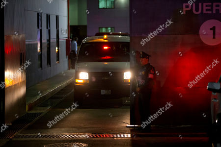 """A police officer stands guard as a vehicle leaves from the airport hangar of Mexico's Attorney General office, in Mexico City, after the arrival of drug lord Hector """"El Guero"""" Palma, . Palma, one of the founders of the Sinaloa Cartel, returned to his native country Wednesday after serving almost a decade in a U.S. prison. U.S. authorities handed over Palma in Matamoros, across the border from Brownsville, Texas, before flying him to Mexico City for transfer to Altiplano maximum security prison"""
