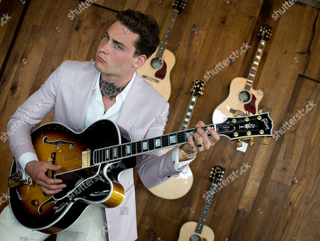 Stock Photo of Dutch singer-songwriter Douwe Bob tries out a Gibson guitar during the official opening of the European hub of Gibson Brands at the A'dam Tower in Amsterdam, Netherlands