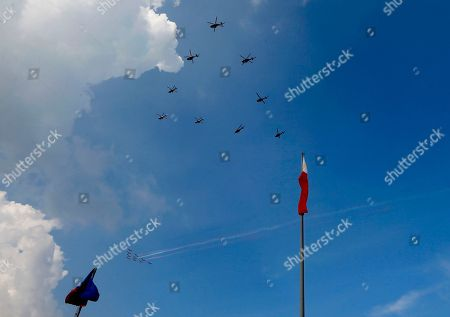 Philippine Air Force S-211 trainer planes, bottom, and UH-1H helicopters make a flyby during the flag-raising and wreath-laying rites to celebrate the 118th Philippine Independence Day at the Rizal Park in Manila, Philippines. Philippine President Benigno Aquino III led the rites for the last time as he is to relinquish his presidency to President-elect Rodrigo Duterte at the end of the month
