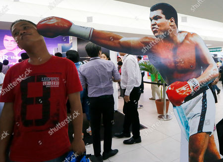 "A Filipino fan poses before a standee of Muhammad Ali during the launch of an exhibit of photos and memorabilia of the ""Thrilla in Manila"" World Heavyweight boxing fight between Muhammad Ali and Joe Frazier at The Ali Mall in suburban Quezon city northeast of Manila, Philippines . The exhibit was launched to pay tribute to Muhammad Ali who died exactly a week ago Friday"