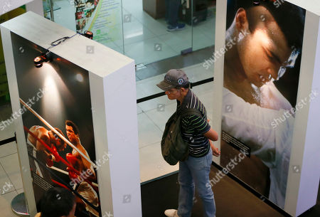"A Filipino fan looks at photos and memorabilia from the ""Thrilla in Manila"" World Heavyweight boxing fight between Muhammad Ali and Joe Frazier at the launch of an exhibit at The Ali Mall in suburban Quezon city northeast of Manila, Philippines . The exhibit was launched to pay tribute to Muhammad Ali who died exactly a week ago Friday. The fight was dubbed the ""Most Legendary Fight in History"