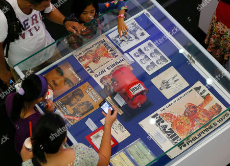 "Stock Image of Filipino fans look at the memorabilia from the ""Thrilla in Manila"" World Heavyweight boxing fight between Muhammad Ali and Joe Frazier at the launch of an exhibit at The Ali Mall in suburban Quezon city northeast of Manila, Philippines, . The memorabilia includes autographed boxing gloves, tickets, souvenir programs, news clippings and commemorative stamps. The fight was dubbed the ""Most Legendary Fight in History"