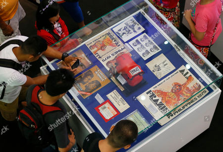 """Stock Photo of Filipino fans look at the memorabilia from the """"Thrilla in Manila"""" World Heavyweight boxing fight between Muhammad Ali and Joe Frazier at the launch of an exhibit at The Ali Mall in suburban Quezon city northeast of Manila, Philippines, . The memorabilia includes autographed boxing gloves, tickets, souvenir programs, news clippings and commemorative stamps. The fight was dubbed the """"Most Legendary Fight in History"""