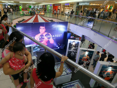 "Stock Picture of Filipino fans look at memorabilia from the ""Thrilla in Manila"" World Heavyweight boxing fight between Muhammad Ali and Joe Frazier at the launch of an exhibit at The Ali Mall in the suburban Quezon city northeast of Manila, Philippines on . The fight was dubbed the ""Most Legendary Fight in History"