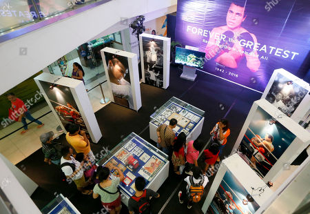 "Filipino fans look at memorabilia from the ""Thrilla in Manila"" World Heavyweight boxing fight between Muhammad Ali and Joe Frazier at the launch of an exhibit at The Ali Mall in suburban Quezon city northeast of Manila, Philippines to pay tribute to Muhammad Ali who died exactly a week ago . The fight was dubbed the ""Most Legendary Fight in History"