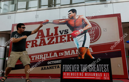 "Romy Doria Romy Doria poses before a standee of Muhammad Ali during the launch of an exhibit of photos and memorabilia from the ""Thrilla in Manila"" World Heavyweight boxing fight between Muhammad Ali and Joe Frazier at The Ali Mall and the Smart Araneta Coliseum in suburban Quezon city northeast of Manila, Philippines . The exhibit was launched to pay tribute to Muhammad Ali who died exactly a week ago Friday"