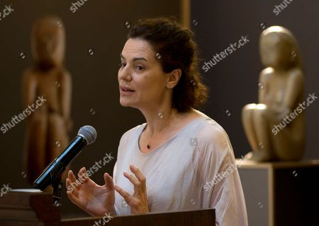 """Actress Maia Morgenstern speaks backdropped by the """"Wisdom of the Earth"""" sculpture by Constantin Brancusi, on display at the National Bank of Romania in Bucharest, Romania, in a bid to raise public funds to purchase one of the artist's greatest artworks. The campaign has raised some 212,000 euros ($237,000) since March when it began, a fraction of the 11-million-euro purchase price of which Romania's government will pay 5 million euros"""