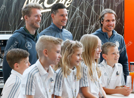 Stock Picture of Andre Schuerrle, Julian Draxler and assistant coach Thomas Schneider, from left, pose with children after a press conference in Evian, France, where the German team is based . Germany will face the Ukraine in a Euro 2016 Group C soccer match in Lille on Sunday, June, 12, 2016