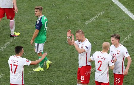 Northern Ireland's Jamie Ward, top, looks on as Poland's Slawomir Peszko, Kamil Glik, Michal Pazdan and Lukasz Piszczek, from left, celebrate after winning 1-0 during the Euro 2016 Group C soccer match between Poland and Northern Ireland, at the Allianz Riviera stadium, in Nice, France