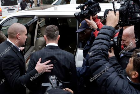 Oscar Pistorius, center, is escorted into a car after the first day of his sentencing hearing at the high court in Pretoria, South Africa, . Pistorius appeared in a South African court on Monday for a sentencing hearing after the double-amputee Olympian was convicted of murdering girlfriend Reeva Steenkamp. Defense lawyer Barry Roux argued for some leniency and called a psychologist who evaluated Pistorius to testify