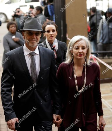 Oscar Pistorius' uncle Arnold Pistorius, left, with wife Lois, right, arrives at the High Court in Pretoria, South Africa, for sentencing proceedings. An appeals court found Pistorius guilty of murder, and not culpable homicide for the shooting death of his girlfriend Reeve Steenkamp