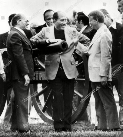 Talking with Begin and Carter Gettysburg. Talking over a Gun barrel. Egyptian President Anwar Sadat, center, leans on the barrel of a cannon as he talks with Israeli Prime Minister Menachem Begin, left, and President Carter during a tour of the Gettysburg Batterfield Sunday. Undated picture