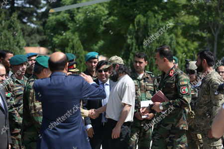 Ali Haidar Gilani, center, son of former Pakistani Prime Minister Yusuf Raza Gilani, center, shakes hand with Afghan officials as he arrives at the Afghan Ministry of Defense in Kabul, Afghanistan, . Gilani, who was freed from kidnappers in a dramatic military rescue in Afghanistan has been handed over to Pakistan's ambassador in Kabul