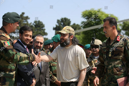 Ali Haidar Gilani, center, son of former Pakistani Prime Minister Yusuf Raza Gilani, shakes hand with Afghan officials as he arrives at the Afghan Ministry of Defense in Kabul, Afghanistan, . Gilani, who was freed from kidnappers in a dramatic military rescue in Afghanistan has been handed over to Pakistan's ambassador in Kabul