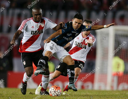 Stock Image of Jonny Uchuari of Ecuador's Independiente del Valle, center, fights for the ball with Andres D'Alessandro, right, and Eder Alvarez Balanta of Argentina's River Plate during a Copa Libertadores soccer match in Buenos Aires, Argentina