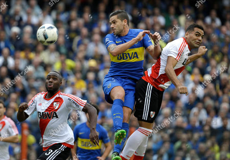 Eder Alvarez Balanta, left, and Gabriel Mercado, right, of River Plate fights for the ball with Fernando Gago of Boca Juniors during an Argentina league soccer match in Buenos Aires, Argentina