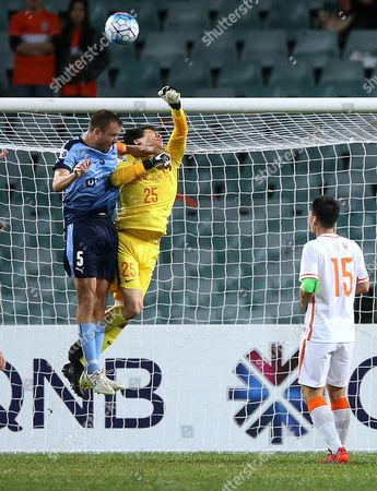 Shandong Luneng Taishan FC's goalkeeper Wang Dalei, center, punches the ball away before Sydney FC's Matthew Jurman, left, can head the ball during their round of 16 match of the Asian Champions League soccer in Sydney