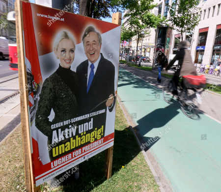 Stock Photo of A cyclist drives past an election poster of businessman Richard Lugner with his wife Cathy Lugner, independent candidate for presidential elections, in Vienna, Austria. For the first time, Austria's next president will likely be someone who is not officially backed by one of the two parties that have dominated government since the end of World War II. That reflects massive voter unhappiness _ and spells possible political turmoil ahead